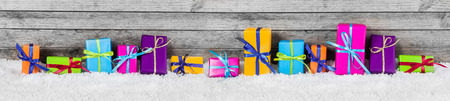 Panorama View of Beautiful Colored Gift Box Decorations on the Snow with Vintage Wooden Wall Behind. photo
