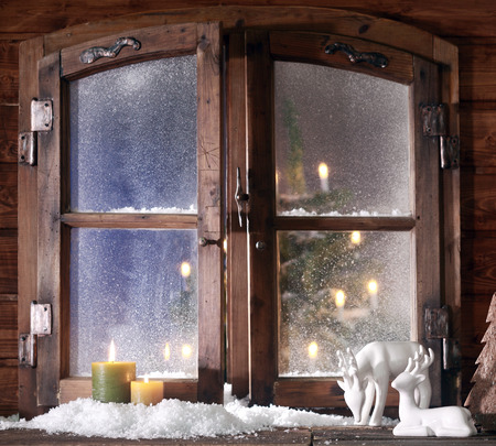 Christmas Items - Snow Formed Reindeer and Colored Lighted Candles at Wooden Window Pane with Glowing Christmas Tree at the Back. Stock Photo