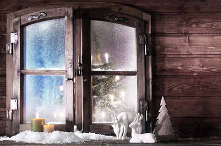 winter window: Christmas Decorations - Snow Formed Reindeer, Christmas Tree and Lighted Candles - at Vintage Wooden Window Pane with Glowing Big Christmas Tree at the Back.