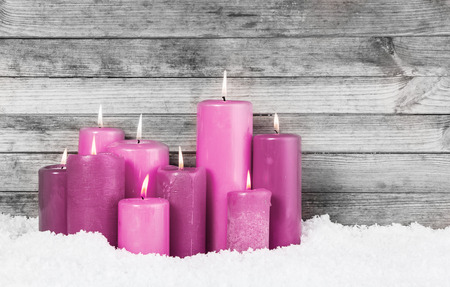 Close up Red Violet Lighted Candles for Christmas Decorations on the Snow with Vintage Wooden Wall Background. photo
