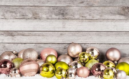 Close up Attractive Shiny Brown and Green Christmas Ball Decorations on the Snow with Vintage Wooden Wall Behind. photo