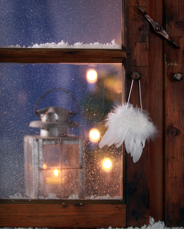 guiding light: Close up Pure White Feathers Hanging on Vintage Wooden Window Pane During Christmas. Stock Photo