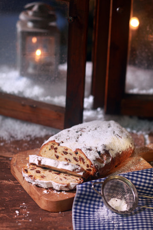 window pane: Close up Sweet Sliced Bread with Raisins and Sugar on Wooden Chopping Board, Placed Near the Window Pane. Stock Photo