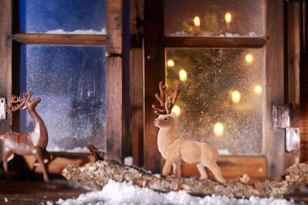 window pane: Close up Reindeer Decors for Yuletide Season at Window Pane with Glowing Christmas Tree at the Back.