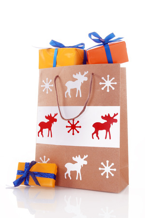 overflowing: Close up Christmas Paper Bag with Orange Gift Boxes. Isolated on White Background.