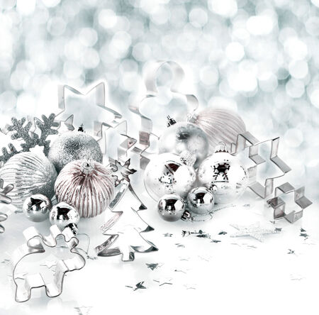 cookie cutter: Stylish silver Christmas background still life with assorted cookie cutters and metallic silver baubles and a snowflake in fresh winter snow with a bokeh of falling snowflakes with copyspace Stock Photo