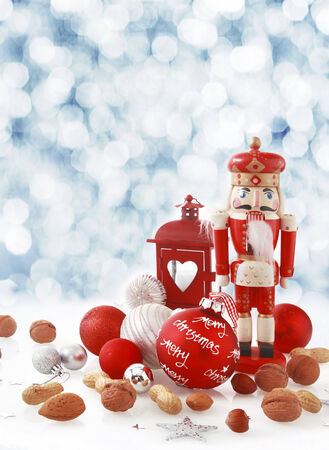 the nutcracker: Colorful red Christmas still life of a traditional wooden nutcracker in the form of a king amongst assorted fresh nuts, baubles and a Xmas lantern in winter snow with a bokeh of falling snow behind