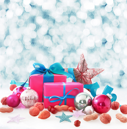Christmas still life of colorful pink and blue gifts, stars, baubles and nuts in winter snow with a bokeh of falling white snowflakes behind and copyspace for your Xmas wishes photo