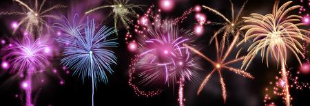 Färgglada fyrverkeri av raketer spricker i en skur av brinnande spår och gnistor i en natthimlen för att fira en festival eller helgdag som nyårs eller Day of Independence Stockfoto
