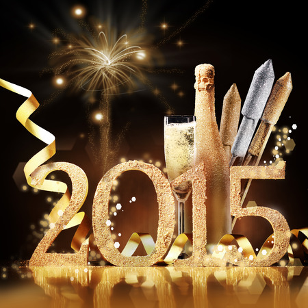 skoal: 2015 New Yeas Eve celebration still life in elegant gold with the date, a flute and bottle of champagne and rockets in front of a brown background with a pyrotechnic display of bursting fireworks