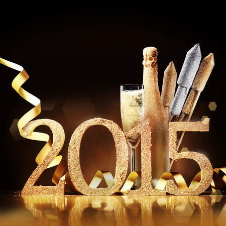 skoal: Stylish gold themed 2015 New Year background with the date in numbers, an elegant flute and bottle of champagne, fireworks and a coiled golden ribbon over brown with copyspace for your greeting