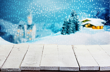 scenery: Empty rustic white painted wooden table with rough boards against a winter Christmas scene of a log cabin and church in snowy mountain scenery with glowing windows for product placement
