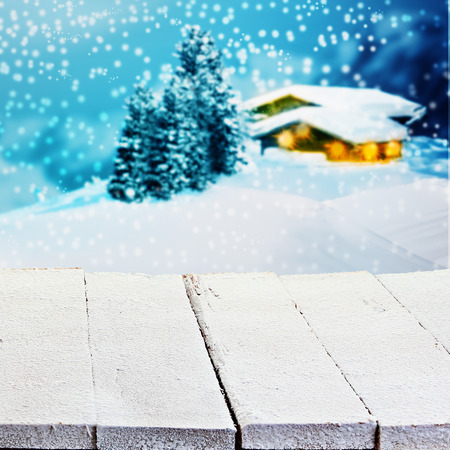 forest products: Winter or Christmas advertising background with empty white painted rustic wooden boards overlooking a lighted snowy timber mountain cabin with falling snow for product placement Stock Photo
