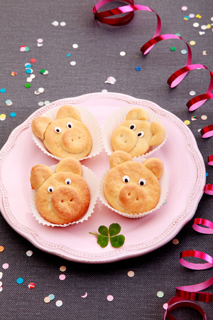 porker: Delicious Cute Cookies Forming Small Pigs on Pink Plate Served on Gray table with Colorful Sequences and Spiral Red Foil.