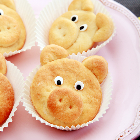 porker: Close Up Fresh Tasty Cute Pig Cookies on White Liners, Prepared on Pink Plate.