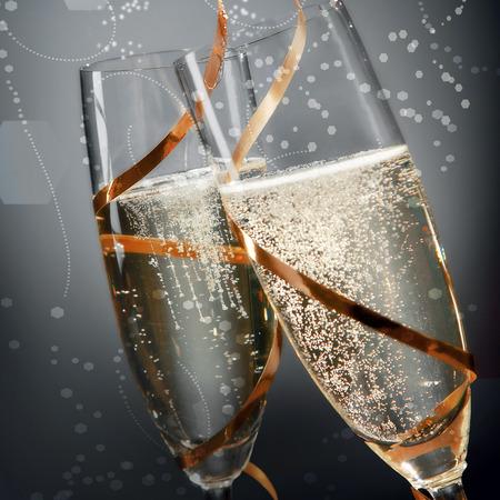 brindisi spumante: Flauti romantiche di frizzante champagne d'oro con le bollicine effervescenti avvolto in nastro d'oro per celebrare un matrimonio, San Valentino, Capodanno o anniversario, da vicino i dettagli sul grigio