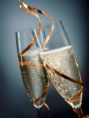 skoal: Toasting with sparkling golden champagne in glass flutes wrapped with elegant gold ribbon for New Year, anniversary, wedding or Valentines, close up view