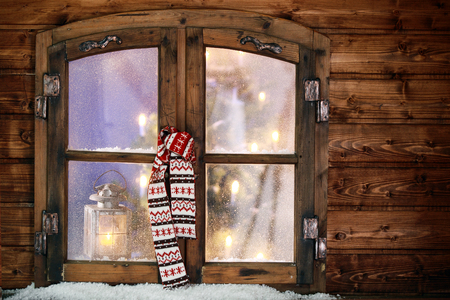 windowpanes: Colorful patterned knitted winter scarf hanging in a Christmas window with the glowing lights of a decorated Christmas tree visible through the frosted windowpanes Stock Photo