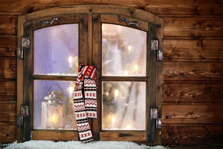 adentro y afuera: Colorido patrón de punto colgante bufanda de invierno en una ventana de la Navidad con las luces brillantes de un árbol de Navidad decorado visibles a través de los cristales esmerilados Foto de archivo