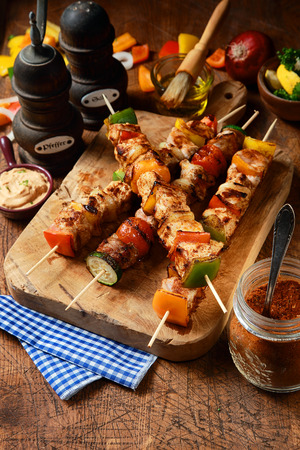 Delicious barbecued or grilled meat kebabs with onion and colorful bell pepper on a rustic wooden board surrounded by ingredients, marinade and seasoning