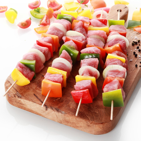 Beautifully presented fresh meat and vegetable kebabs with diced colorful sweet bell pepper and onion standing ready for grilling or roasting on a wooden board over white photo