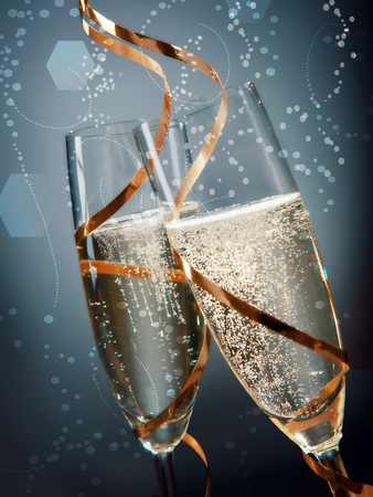 skoal: New Years Concept - Close up Pair of Wine Glasses with Gold Laces Around on Abstract Blue Gray Background. Stock Photo