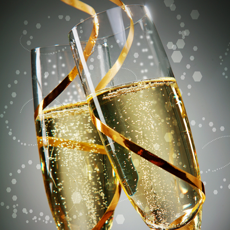 skoal: Close up Golden Wine on Flute Glasses with Gold Laces on Abstract Gray Background. A New Years Day Concept Design.