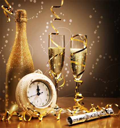effervescence: Elegant gold New Year still life with a clock counting down to midnight in front of a bottle and flutes of sparkling champagne with golden streamers and a bokeh of effervescent bubbles