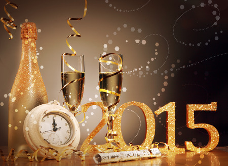 greeting season: 2015 New Years Eve celebration background with an elegant arrangement with a clock counting down to midnight, flutes and bottle of champage and party streamers with a cracker, bubble bokeh Stock Photo