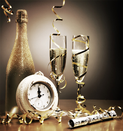 Stylish gold still life depicting the countdown to midnight on New Years Eve with a clock, party cracker, streamers and flutes and a bottle of golden champagne to celebrate