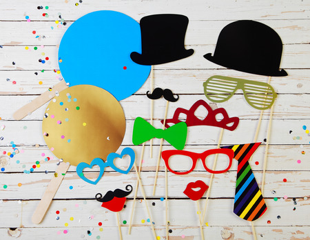 photo of accessories: Trendy colorful party background of fun photo booth accessories for comic disguise and multicolored confetti on rustic white wooden boards