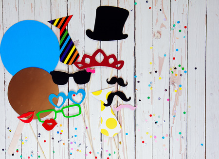 Photo booth accessory background with colorful paper fashion accessories, lips, and moustaches on white wooden background sprinkled with multicolored party confetti with copyspace for your text