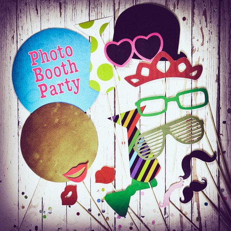 Fun photo booth party background with colorful paper fashion accessories, lips, moustaches and balloons with text - Photo Booth Party - surrounded by a vignette, square format Banco de Imagens