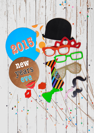 2015 New Years Eve photo booth party background with a festive array of clothing accessories for fun fancy dress on a rustic white wooden panel and copyspace below photo