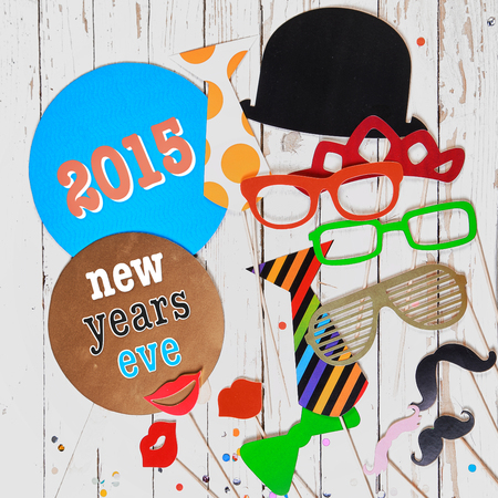 2015 News Years Eve carnival background with comic colorful photo booth paper fashion accessories for a fun party disguise photo
