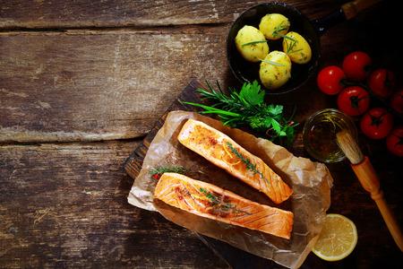 Obenliegende Ansicht der köstlichen gegrillten herzhaften Lachskoteletts mit Zutaten, einschließlich einem Bouquet garni von frischen Kräutern, Olivenöl, Tomaten, Baby-Kartoffeln und Zitrone auf einem rustikalem Holztisch mit Exemplar