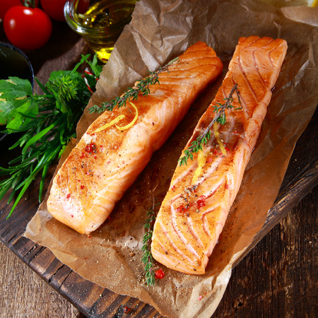 marinate: View from above or two succulent grilled salmon steaks seasoned with herbs on crumpled brown paper in a rustic kitchen with herbs, tomatoes and olive oil