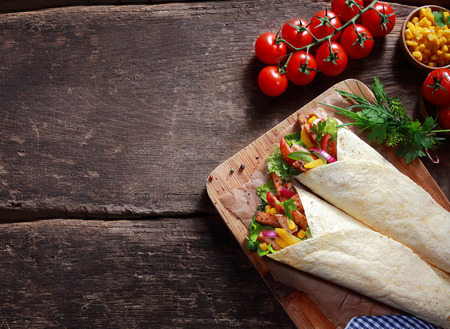 Preparing tasty Tex-Mex tortilla wraps in a rustic kitchen filled with fresh salad ingredients, corn kernels, herbs and diced meat , overhead view with ingredients and copyspace