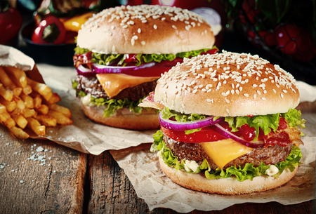 grill: Two cheeseburgers on sesame buns with succulent beef patties and fresh salad ingredients served with French Fries on crumpled brown paper on a rustic wood table