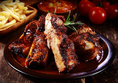 Plate of delicious spicy marinated grilled or barbecued spare ribs served with French Fries and tomato at a steakhouse or restaurant, close up view Stockfoto