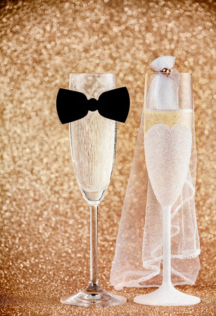 Celebrating a wedding with champagne with two elegant flutes dressed as the bride and groom with a bow tie and veil against a luxury background of sparkling gold bokeh