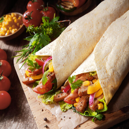 High angle view of two colorful healthy mexican tortillas filled with fresh salad ingredients and diced grilled meat on a wooden chopping board surrounded by ingredients photo