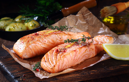 grilled salmon: Gourmet grilled salmon cutlets seasoned with assorted herbs and served on rustic brown paper with lemon, close up showing texture Stock Photo