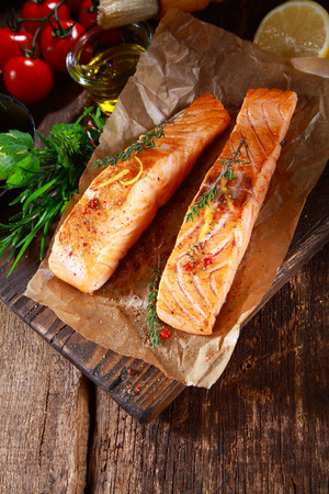 View from above of two succulent grilled salmon steaks on brown paper with fresh herbs, olive oil and tomato on a rustic wooden kitchen table photo