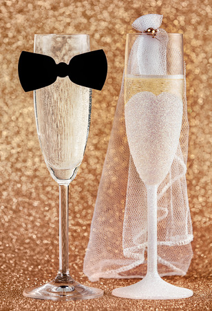 Elegant champagne flutes dressed for a wedding as the bridal couple in a bow tie and veil decorated with gold sparkle in a creative celebration of a marriage