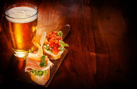 tapas españolas: Vaso de cerveza fría con deliciosas tapas rematado con camarones, jamón de Parma y el tomate en baguette servido en un bar o pub mostrador de madera para aperitivos