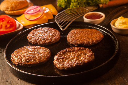 Preparing a batch of cheeseburgers with assorted ingredients and four grilled ground beef patties or frikadeller in a pan Zdjęcie Seryjne