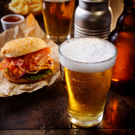 glasses of beer: Glass of chilled beer served with a cheeseburger and French fries for a relaxing lunch in a pub or bar
