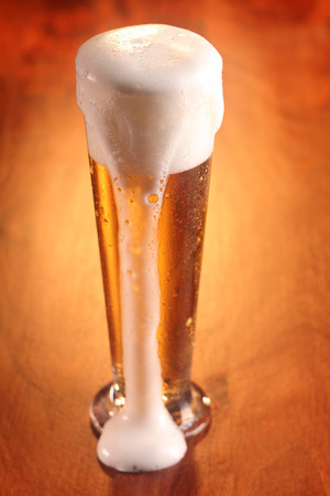 overflowing: Tall elegant glass of beer with overflowing froth running down the side standing on a wooden bar counter, high angle view with highlight behind the glass