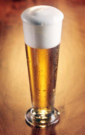 Tall stylish glass of refreshing chilled beer with a good frothy head on a wooden background with vignette, high angle view photo
